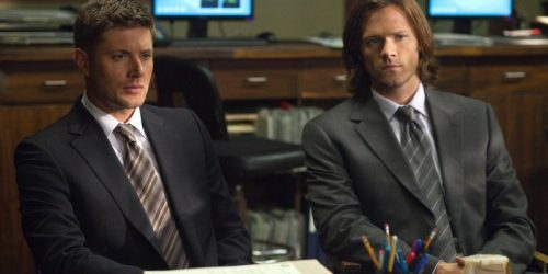 Dean and Sam staring at someone over a desk